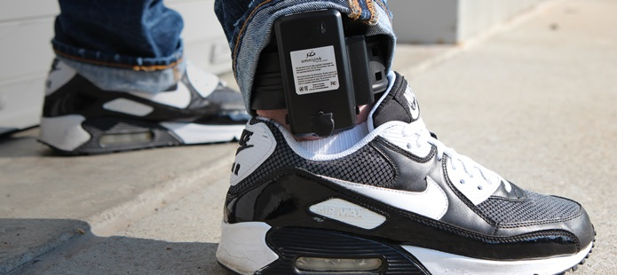 A Southern summer student models the new ankle monitors