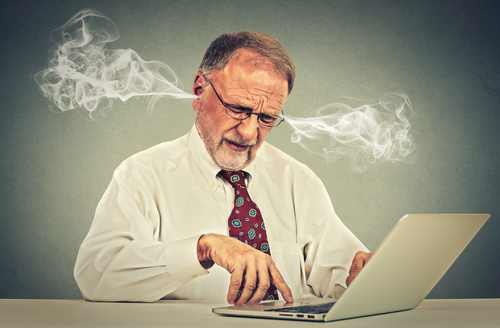Stressed elderly old man using computer blowing steam from ears